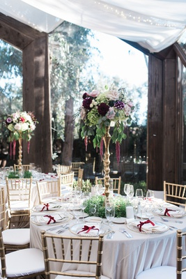 tall centerpiece on gold stand with fall flowers and greenery