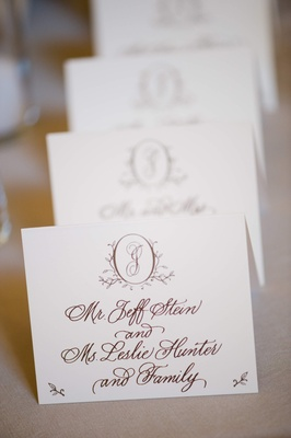 White escort card with brown handwritten calligraphy