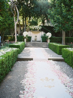 outdoor ceremony space at estate with white aisle runner white pink petals logo with couple name