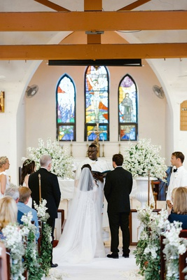 wedding ceremony in little pink chapel harbour island bahamas greenery white flowers altar pews