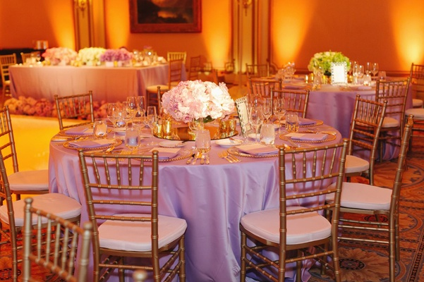 lavender tablecloths with gold chairs and gold lighting
