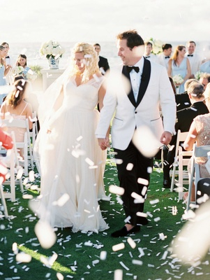 Bride and groom walking up aisle white tuxedo jacket ocean wedding white confetti grass lawn
