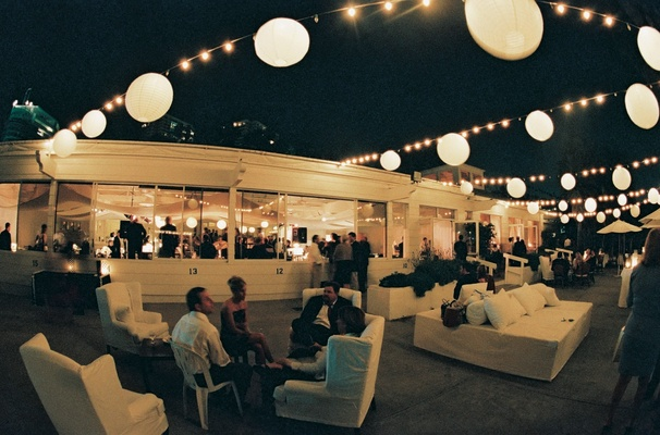 White couches and lanterns adorn a nighttime outdoor reception