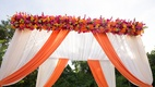 Outdoor Indian wedding ceremony with a white and orange canopy, orange, pink and yellow flowers
