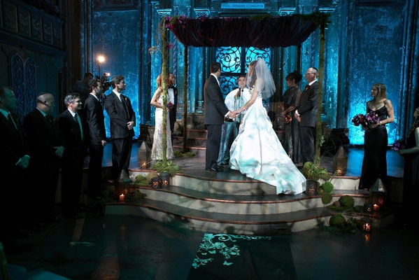 chuppah of greenery stands on raised platform, lit with blue uplighting