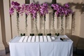 Asian-inspired table with escort cards and purple flowers