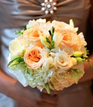 Bridesmaid holds peach flower bouquet with garden roses