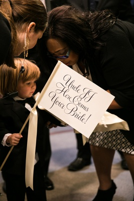 "ring bearer with ""here comes the bride"" sign for his uncle's wedding"