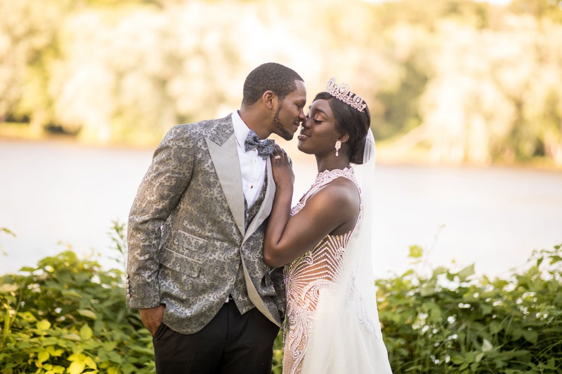 groom in grey patterned tuxedo jacket vest and bow tie bride in high neck gown tiara veil kiss