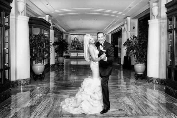 black and white photo of bride in rivini wedding dress and groom in tuxedo