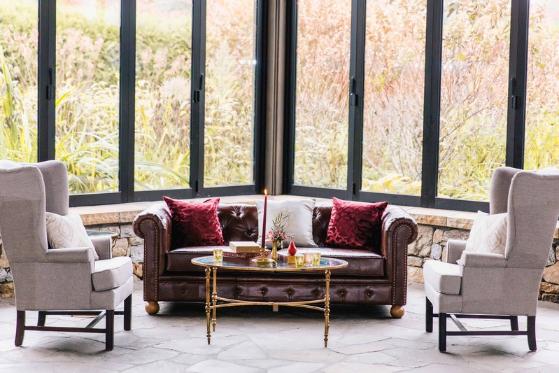 open air space with dark and light colored furniture and tall windows looking outside