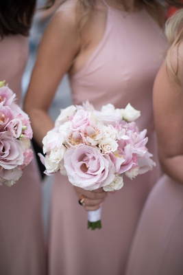 Bridesmaids in pink dresses holding small bouquet of pink rose pink orchid white rose thistle
