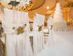 sheer chair covers with a golden clasp at opulent wedding reception
