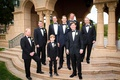 Groom in tuxedo with bow tie with groomsmen on steps of Grand Del Mar
