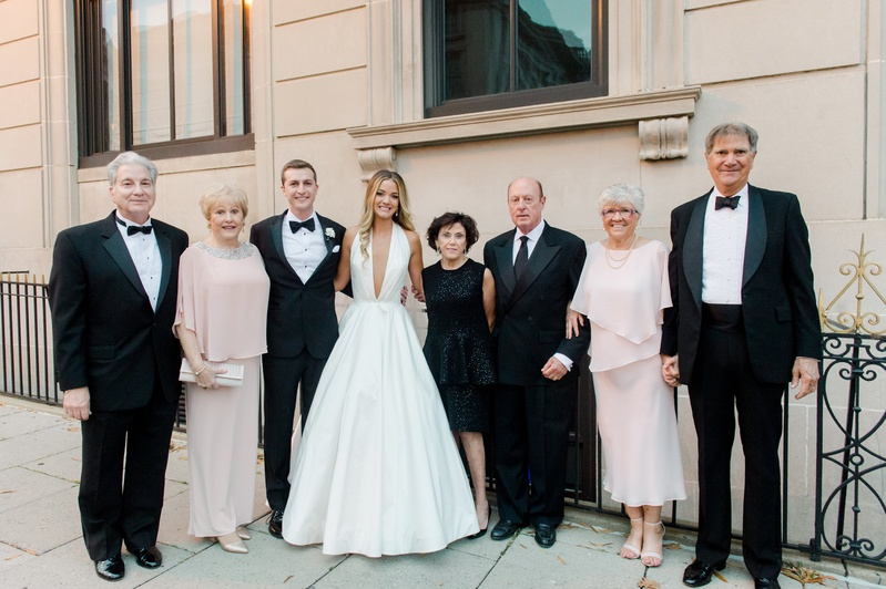 bride in romona keveza a-line gown plunging neckline with groom and families