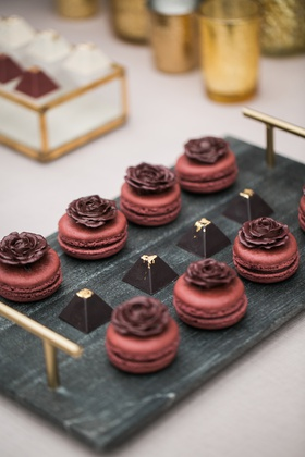 slate tray with maroon macarons with delicate chocolate roses on the top and pyramid truffles
