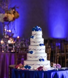 five-tier wedding cake featured frosted blues flowers with grayish lavender detail