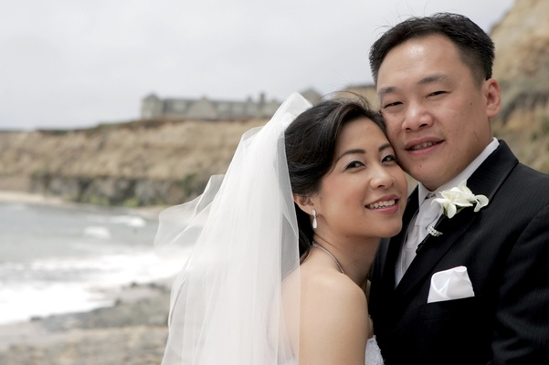 Bride with a veil and groom in a black tuxedo by the beach