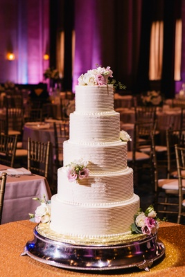five-tier wedding cake with buttercream frosting and fresh flowers