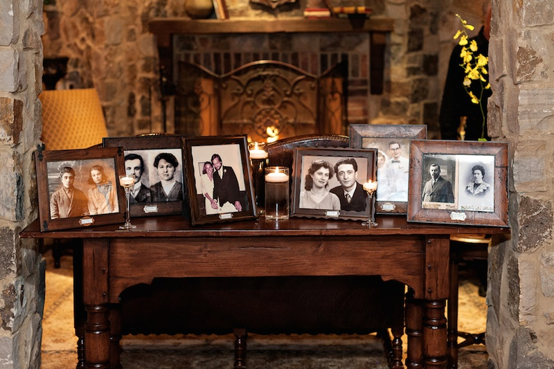 Wood table at wedding reception with portraits of the bride and groom's families