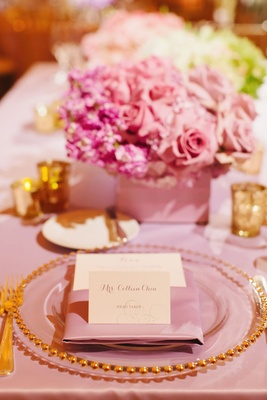 pink tablecloth with pink napkin and gold rimmed charger plate