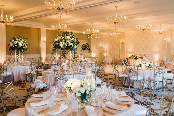 wedding reception ballroom belmond el encanto chandeliers tall centerpiece peach pink white gold