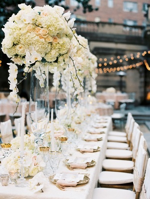 Wedding reception tall centerpiece ivory flowers pink linen napkins gold details taper candles ivory