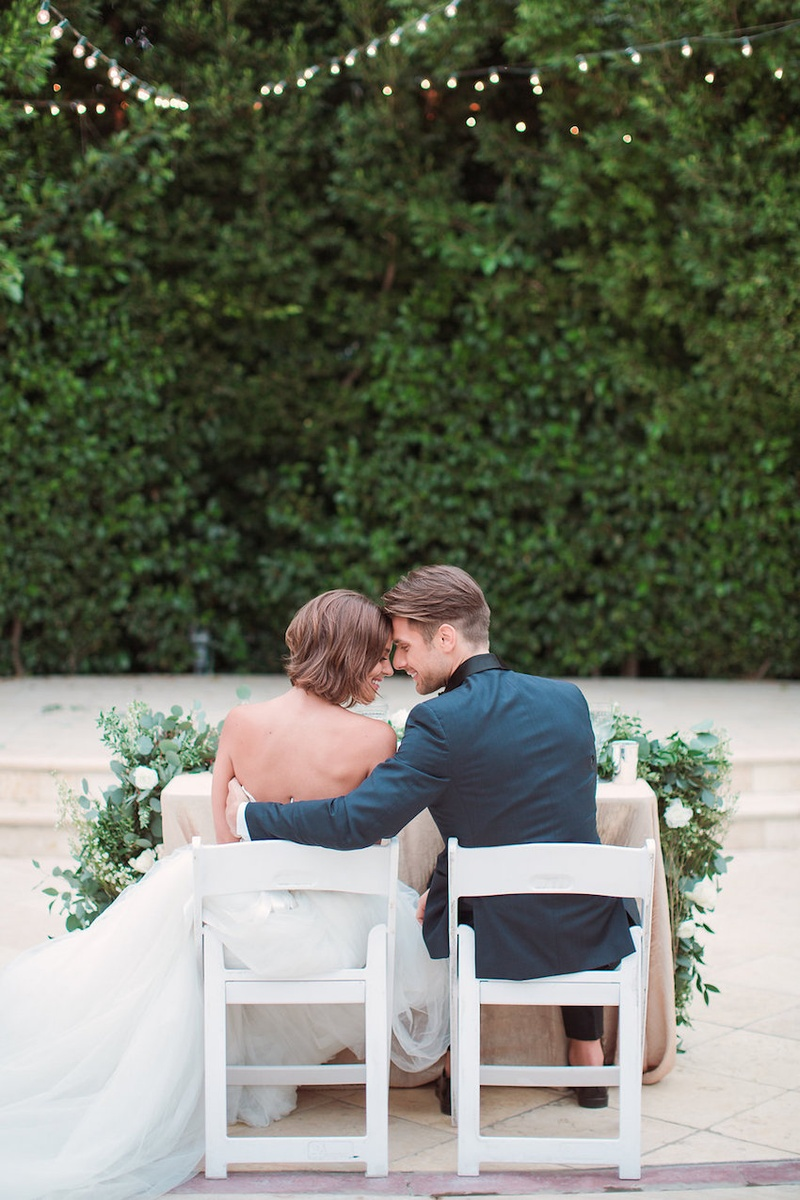 Bride in an Anne Barge wedding dress sits with groom in a teal tuxedo jacket at garden reception