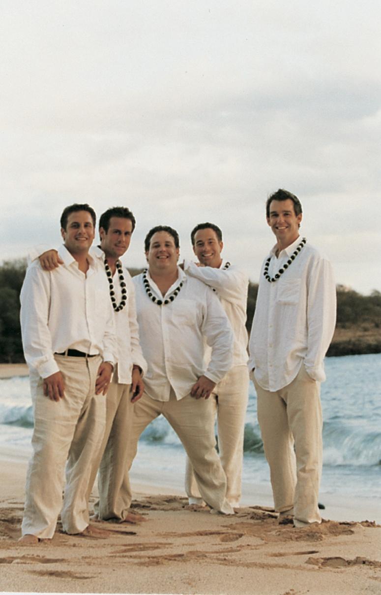 groomsmen wear shell leis on beach in hawaii