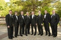 Groom and groomsmen in black tuxedos and ties and bow ties
