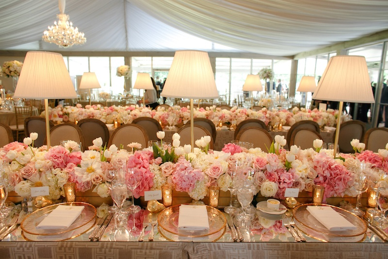 Wedding reception table with mirror top, runner of white hydrangeas, tulips, roses, pink roses