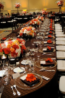 Long oval table with bright floral centerpieces