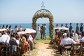 Bride in Ines Di Santo wedding dress under ceremony arch guests with parasols sunny summer wedding