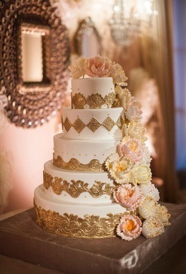 White cake with gold details and sugar flower peonies