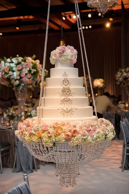 Wedding cake on chandelier swing with crystal rope details and fresh flowers sparkling details