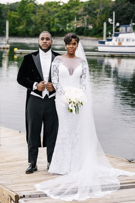 bride in illusion wedding dress long veil sheer long sleeves updo groom in long tail tuxedo
