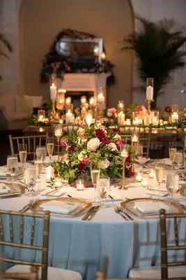 Wedding reception with low centerpieces greenery and burgundy flowers light blue linens gold chairs