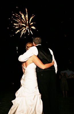 Bride and groom watch firework display