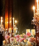 Pink and white flowers and candles line the ledge in front of a mirror at wedding reception