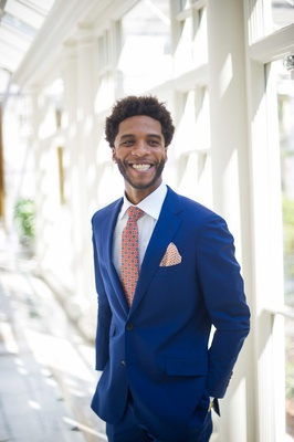 an excited groom smiles in a bright blue tuxedo with orange and blue details on tie pocket square