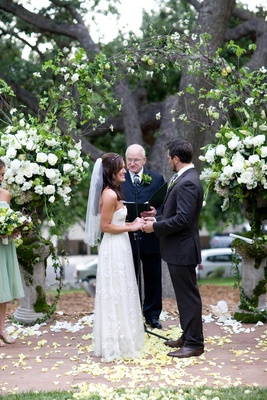 Bride in a Claire Pettibone gown and veil with groom in a pinstripe suit at ceremony