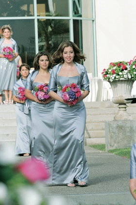 Bridesmaids in silver blue gowns carrying nosegays