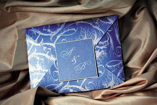 Wedding invitation envelope, in blue with a white pattern, sealed with the couple's monogram