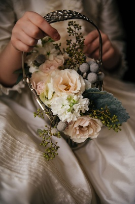 Flower girl holding small basket antique looking with pink white flowers and silver brunia berries