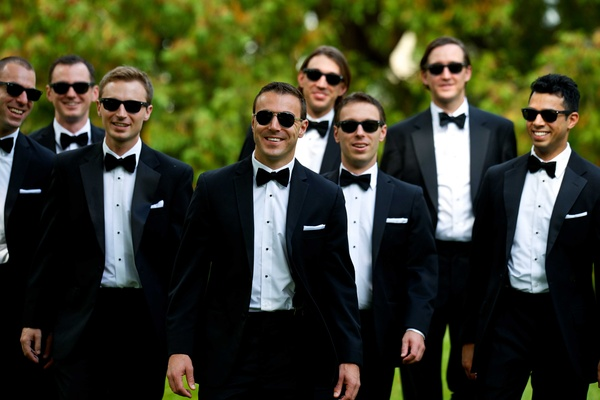 Groom and groomsmen in black tuxedos, bow ties, sunglasses, white pocket squares