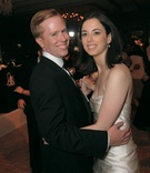 Bride in a ruched strapless dress dances with groom in a black tuxedo