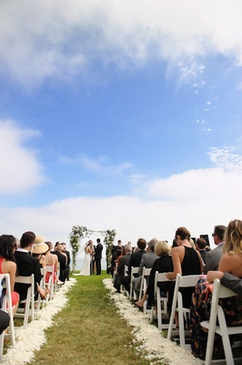 Grass wedding aisle with white flower petals and rustic chuppah