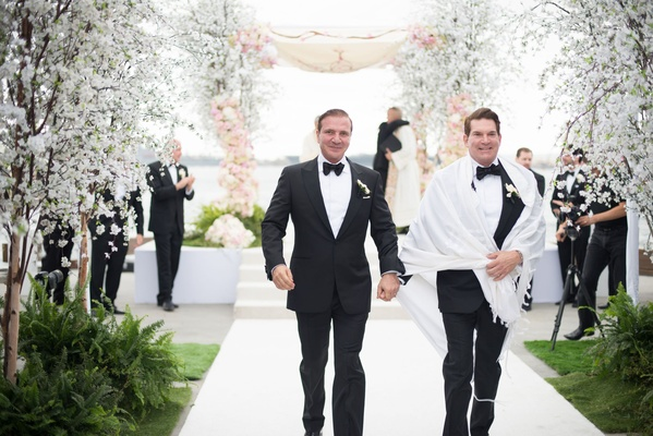 Same sex wedding formal opulent san diego wedding tuxedo holding hands bow ties chuppah white aisle