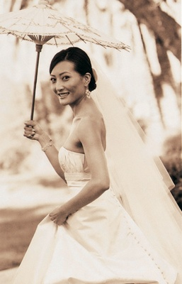Sepia toned photo of bride holding umbrella