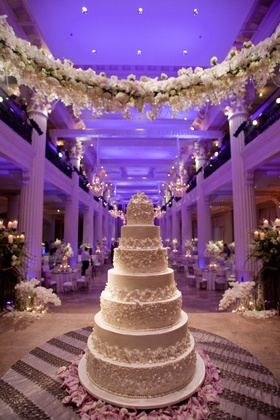White wedding cake under garland of white flowers